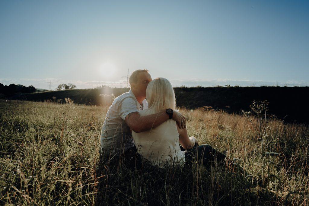sitzendes Paar im Sonnenuntergang, der Mann legt der Frau den Arm um die Schulter