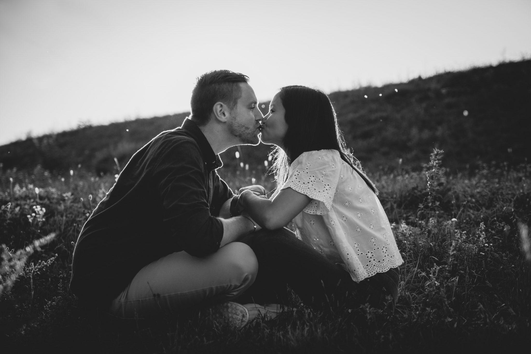 Mann und Frau sitzen sich gegenüber auf der Wiese und küssen sich vorneübergebeugt / schwarz-weiß