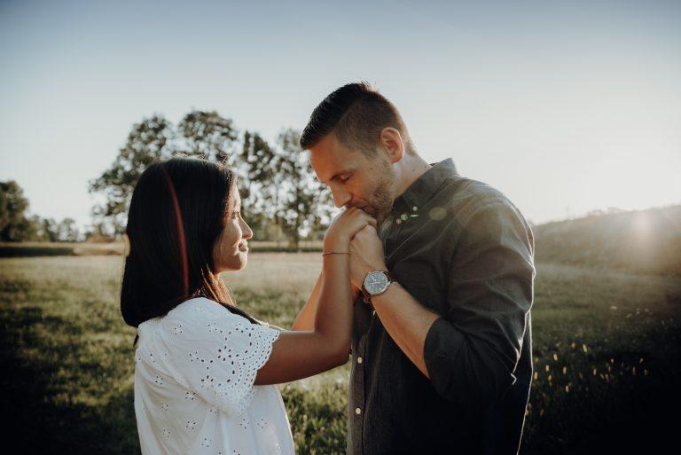 Mann hält und küsst Hände der Frau