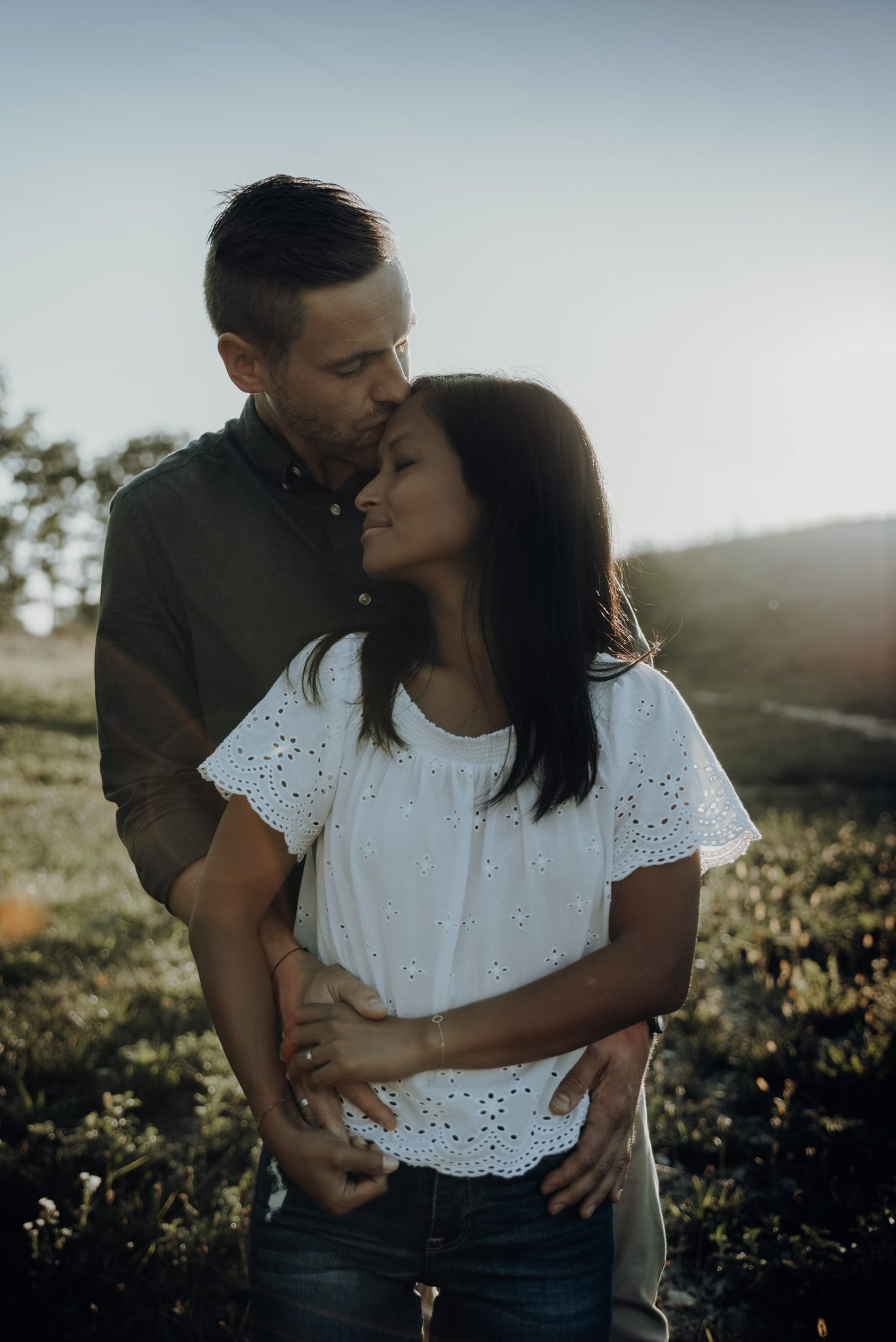 Mann steht hinter Frau und küsst sie auf Stirn
