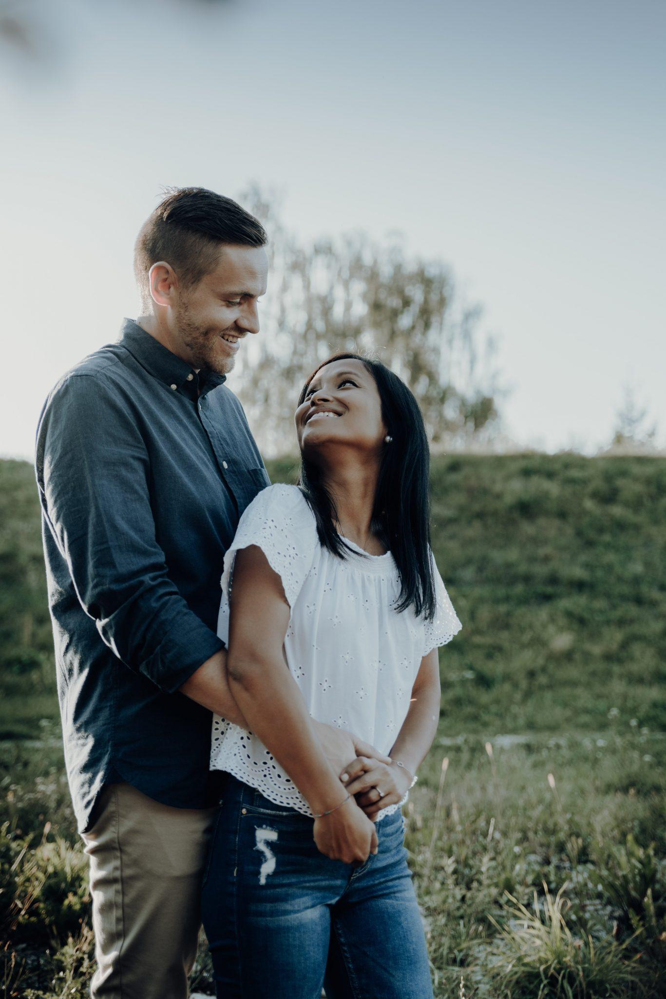 Frau steht vor Mann und lacht ihn über die Schulter schauend an