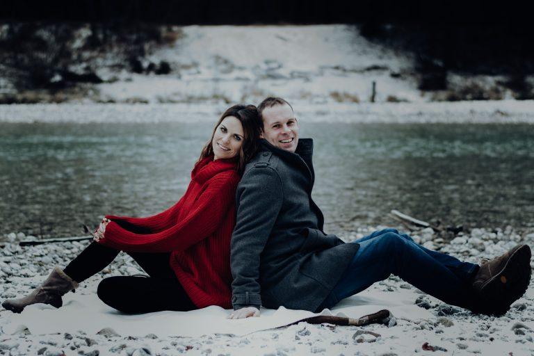 Mann und Frau sitzen Rücken an Rücken am Boden