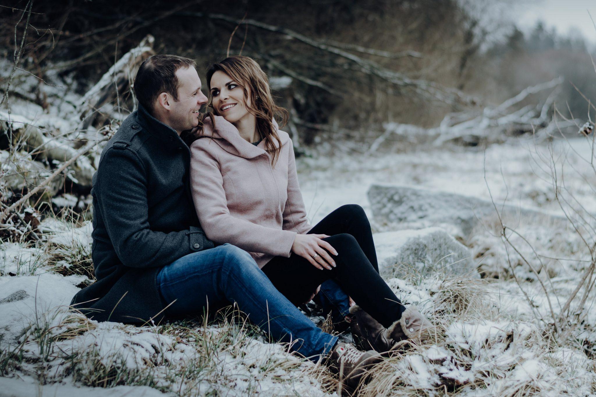 Frau sitzt vor Mann zwischen seinen Beinen