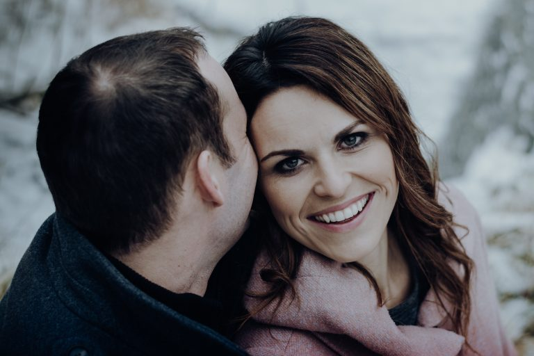 Mann flüstert Frau ins Ohr, sie lacht