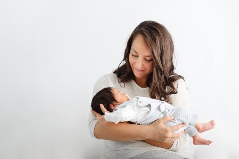 junge Mutter hält schlafendes Baby in Armen und lächelt es glücklich an