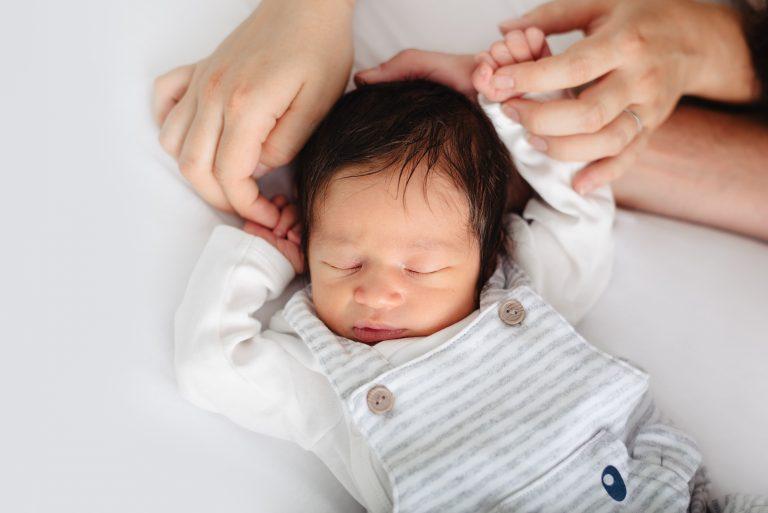 schlafendes Baby umklammert kopfüber Finger der Eltern