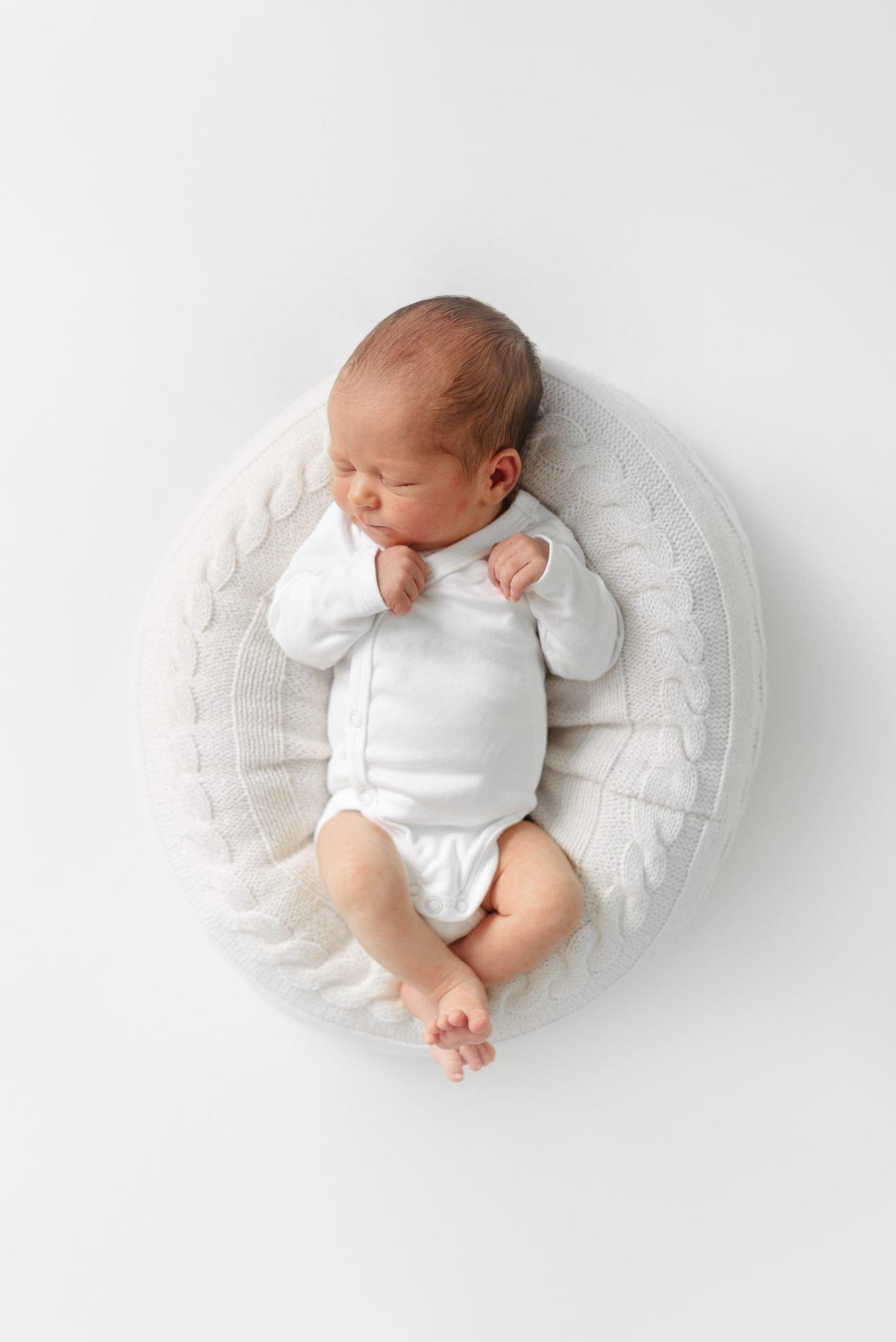 schlafendes Baby in Babynestchen aus der Vogelperspektive
