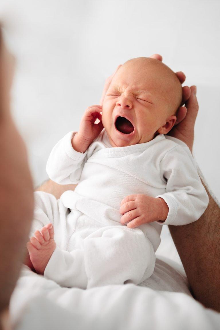 Vater hält gähnendes Baby vor sich